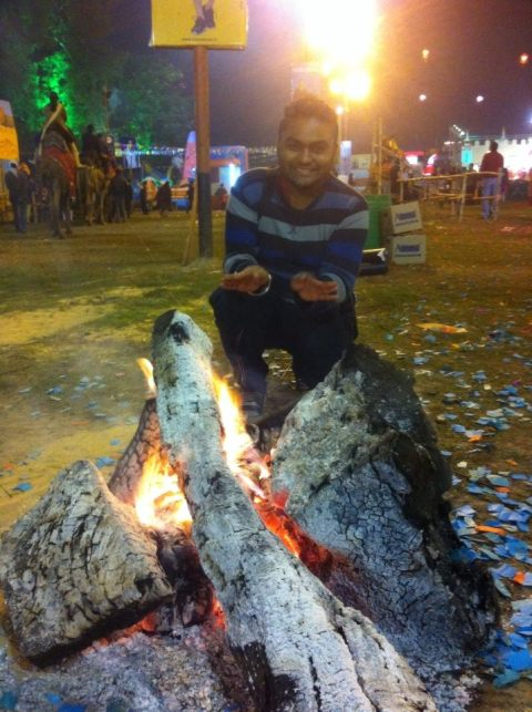 SouBoyy warms his hand at the bonfire at Lok Sanskriti Rajasthani Mela